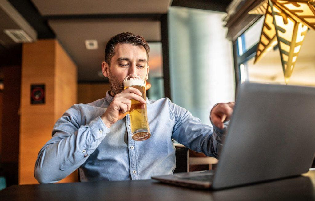 Man taking part in a virtual beer tasting over Zoom