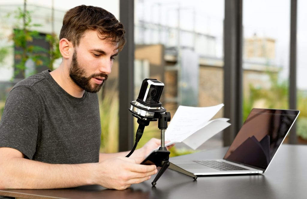 Man speaking into a microphone with a laptop.