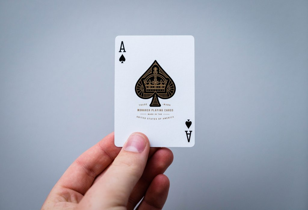 Ace of Spades card held up.