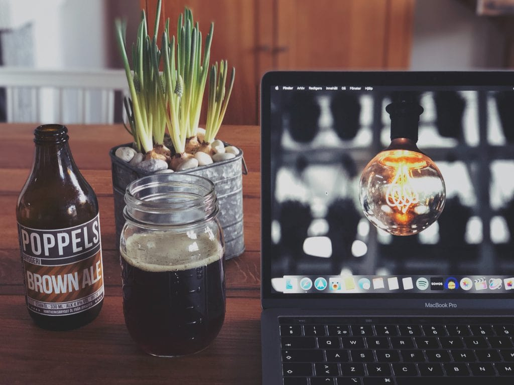 A bottle of beer and an open laptop on a table.