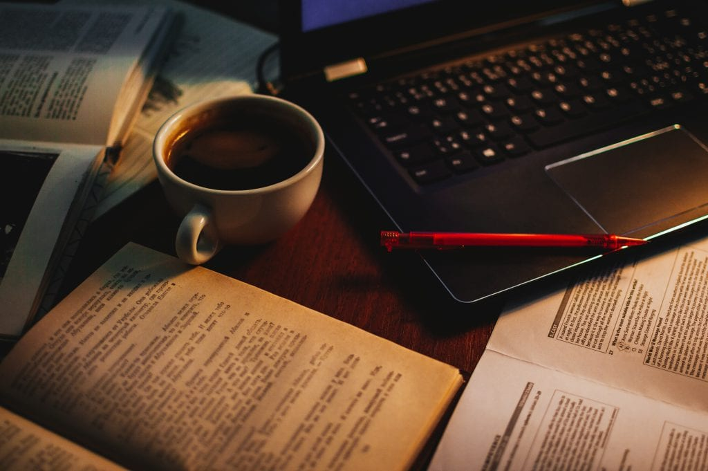 Image of books, papers, a laptop, a coffee and a pen.