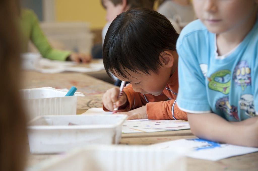 Boy colouring during class.