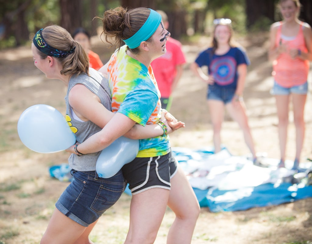 Two girls playing team balloon pop in a 5-minute team building activity in the woods.