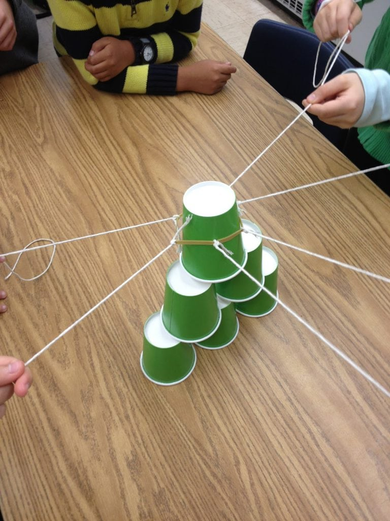 Students playing team cup stack together